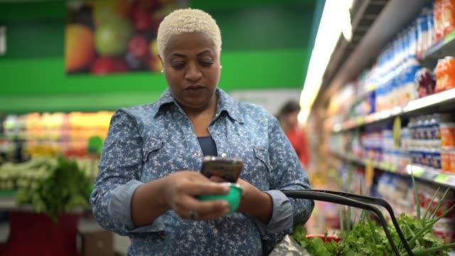vídeos de stock, filmes e b-roll de mulher compra em supermercado usando celular - vale