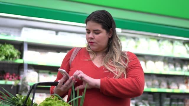 vídeos de stock, filmes e b-roll de mulher compra em supermercado usando celular - consumismo