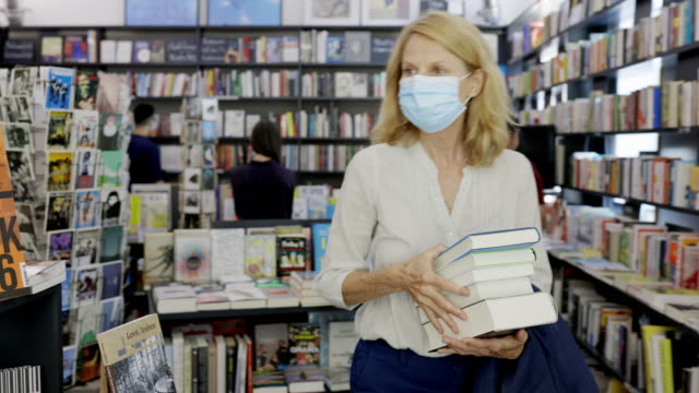 woman buying books at a shop during pandemic - book shop stock videos & royalty-free footage
