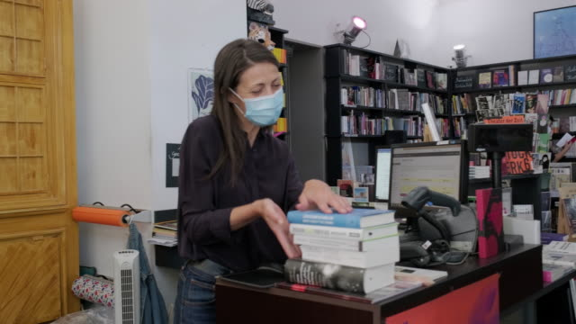 woman buying books at store during pandemic - book shop stock videos & royalty-free footage