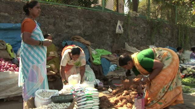 WS Woman buying coconuts at street market / Dharavi Mumbai India