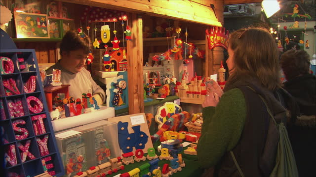 vídeos de stock e filmes b-roll de ms woman buying colorful wooden toys at christmas market / bath, somerset, united kingdom - brinquedo