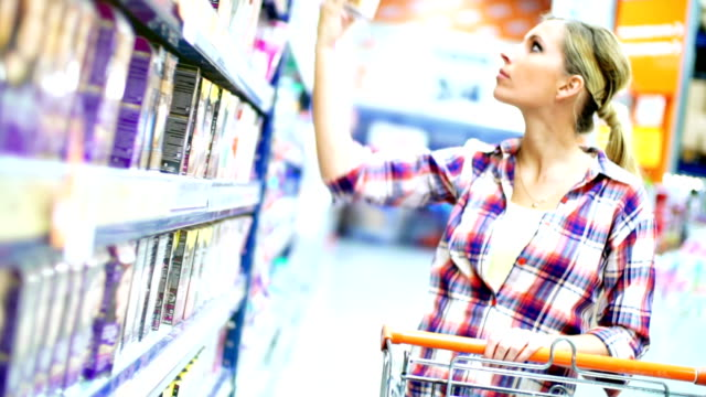 vídeos de stock, filmes e b-roll de mulher comprando produtos cosméticos no supermercado. - pacote arranjo