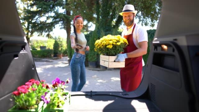 stockvideo's en b-roll-footage met vrouw die bloemen van tuincentrum koopt - bestelwagen
