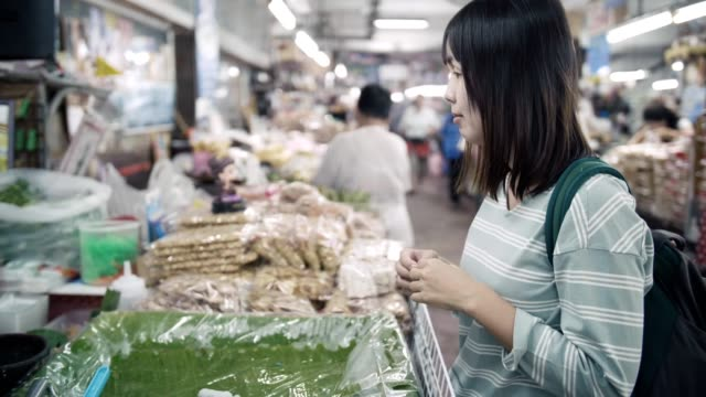 Mujer, compra de alimentos en el mercado de la calle