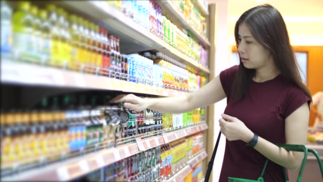 woman buying food in supermarket - nutrition label stock videos and b-roll footage