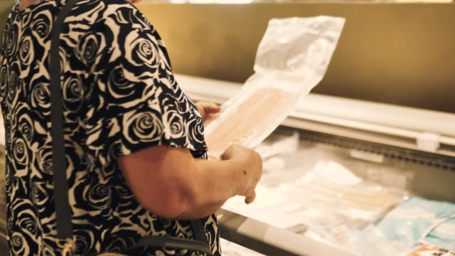 woman buying frozen food in supermarket. - cibi surgelati video stock e b–roll