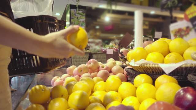 vídeos de stock, filmes e b-roll de mulher comprando frutas no shopping mall - aipo