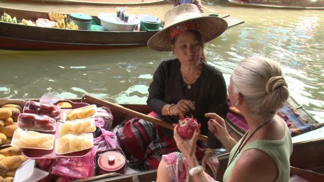 MS Woman buying fruit on Damnoen Saduak floating market, Bangkok, Thailand