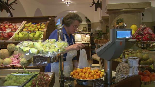ms pan woman buying fruits at dallmayr, luxury delicatessen, munich, bavaria, germany - skåp med glasdörrar bildbanksvideor och videomaterial från bakom kulisserna