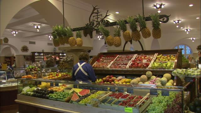 ms woman buying fruits at dallmayr, luxury delicatessen, munich, bavaria, germany - skåp med glasdörrar bildbanksvideor och videomaterial från bakom kulisserna