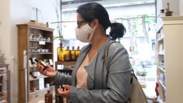 woman buying medicine at drug store during pandemic - entering stock videos & royalty-free footage