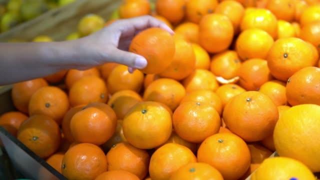 スーパー マーケットのオレンジを買う女 - オレンジ点の映像素材/bロール