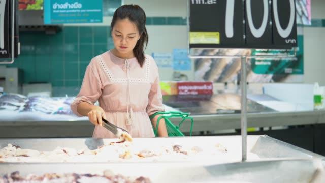 vídeos de stock, filmes e b-roll de mulher comprando mar comida no supermercado - frio