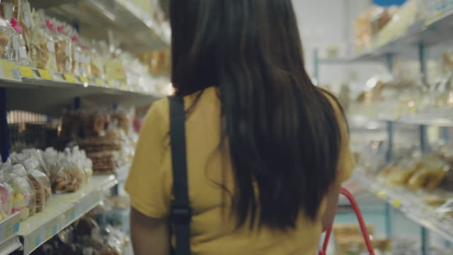 woman buying snacks at supermarket - shopping basket stock videos and b-roll footage