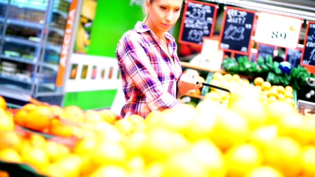 woman buying some fruit in supermarket. - shopping basket stock videos and b-roll footage