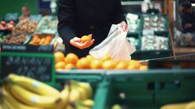 woman buying some fruit in supermarket. - plastic bag stock videos & royalty-free footage