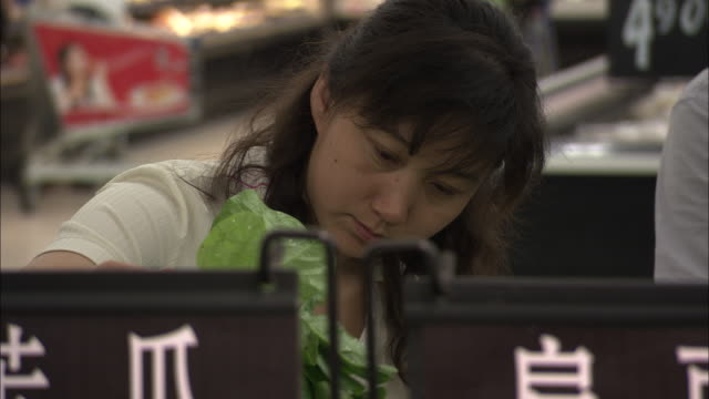 CU Woman buying spinach in supermarket, Beijing, China