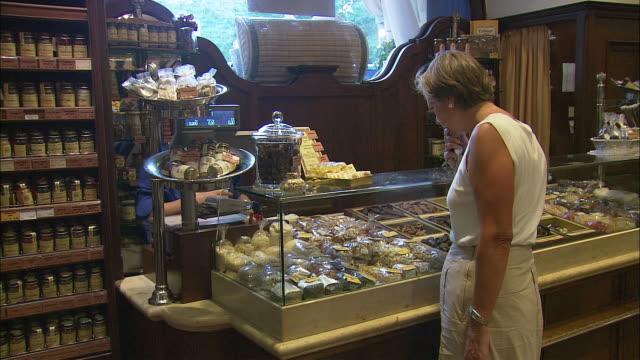 vídeos de stock e filmes b-roll de ms woman buying sweets at dallmayr, luxury delicatessen, munich, bavaria, germany - cristaleira