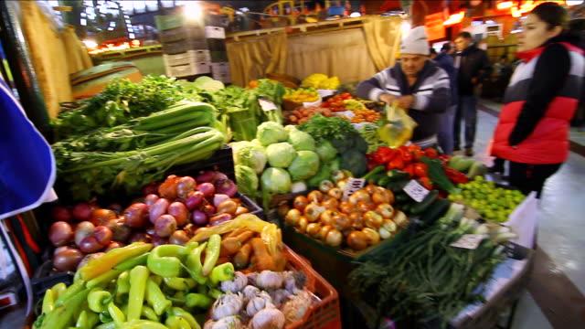 vídeos y material grabado en eventos de stock de ms pan woman buying vegetables from stand at mercado central / santiago, chile - pimientos