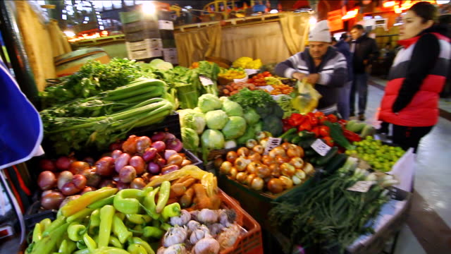 vídeos de stock e filmes b-roll de ms pan woman buying vegetables from stand at mercado central / santiago, chile - pimentão