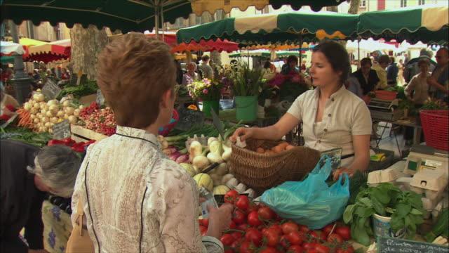vídeos de stock, filmes e b-roll de ms woman buying vegetables in market / aix-en-provence, provence, france - aix en provence