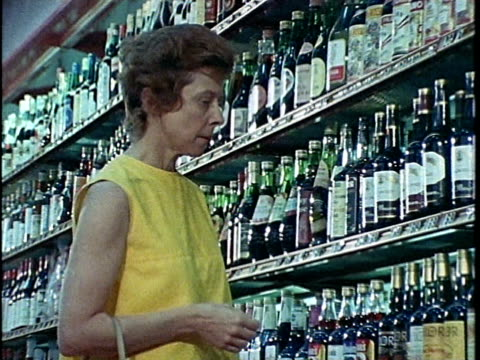 1971 montage woman buying wine in store, pouring wine through funnel into decanter, los angeles, california, usa, audio   - alcohol abuse stock videos & royalty-free footage