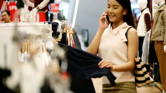 woman buys a shirt in a store - tutti i tipi di top video stock e b–roll