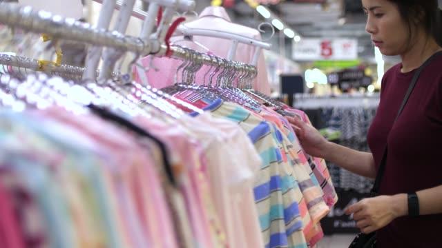 stockvideo's en b-roll-footage met vrouw koopt een shirt - arts culture and entertainment