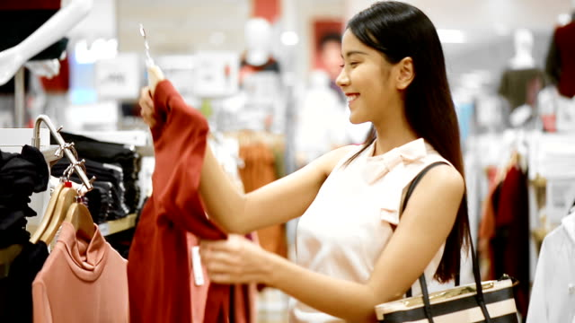 woman buys a t-shirt in the store - top capo di vestiario video stock e b–roll