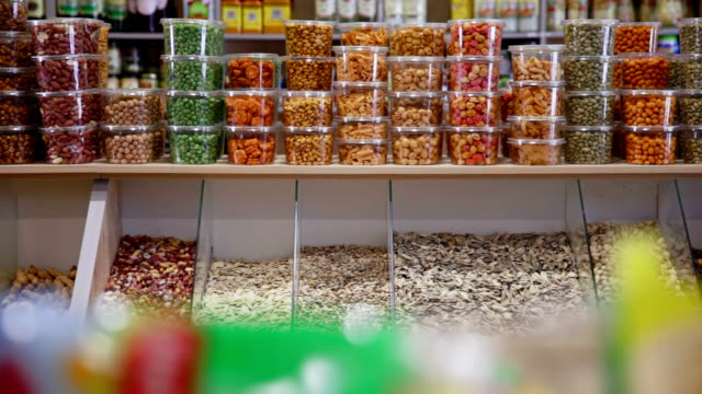 Woman buys jar of nuts and pistachios in grocery