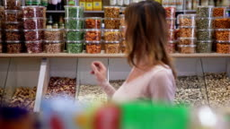 Woman buys jar of nuts in grocery