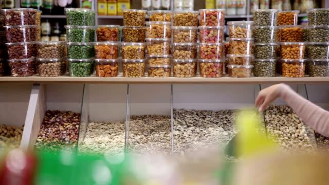 vídeos de stock e filmes b-roll de mulher compras de mercearia sementes de abóbora em - concha utensílio de servir