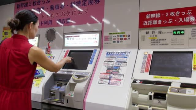 Woman buys train train ticket