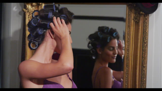 A woman by a mirror with her hair in rollers