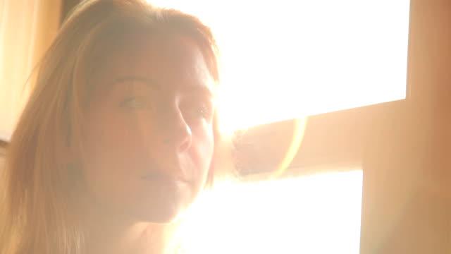 Woman by Bedroom Window Early Morning Sun