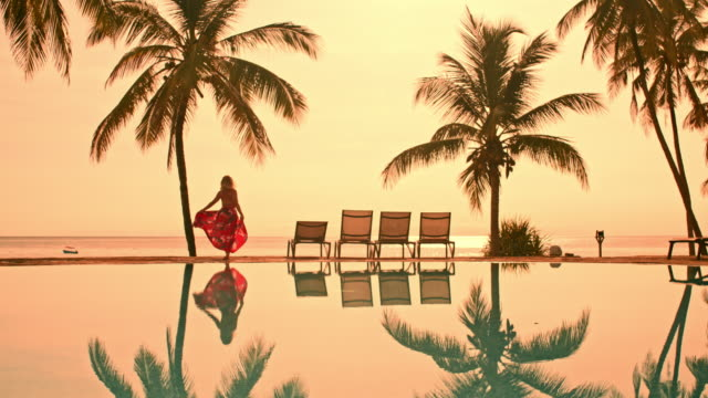 ls woman by the edge of the pool at sunset - infinity pool stock videos & royalty-free footage
