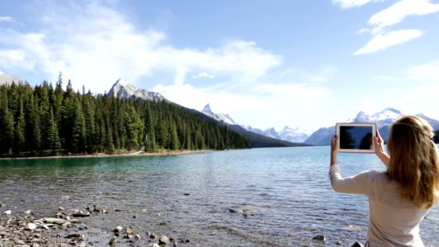 vídeos de stock e filmes b-roll de mulher no lago usando tablet digital para fotografia paisagem - só mulheres jovens