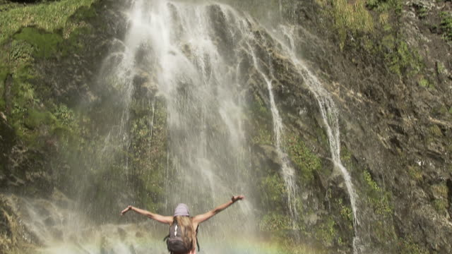 Woman by waterfall with arms open