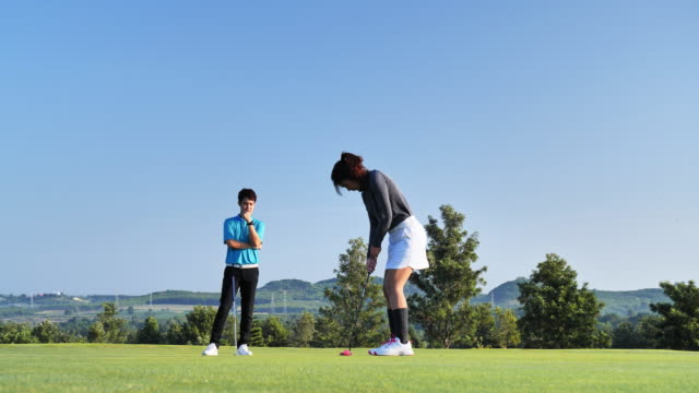 vídeos de stock e filmes b-roll de woman calculating the trajectory of the ball to the hole, while playing professional golf with her male match partner or instructor outdoors in summer - golf