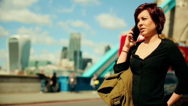 vídeos de stock, filmes e b-roll de mulher chamando no telefone da tower bridge - homem e máquina