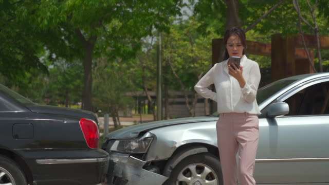 woman calling on the phone after a car accident - 車の故障点の映像素材/bロール