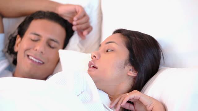 woman can not sleep because of her snoring husband - 横向きに寝る点の映像素材/bロール