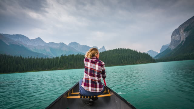 woman canoeing on a pristine lake - pagaiare video stock e b–roll