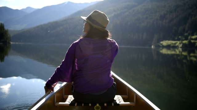 woman canoeing on a pristine lake - canoeing stock videos and b-roll footage