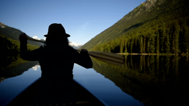 vidéos et rushes de femme, faire du canoë sur un lac vierge - pagayer