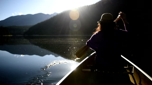 woman canoeing on a pristine lake - traditionally canadian stock videos & royalty-free footage