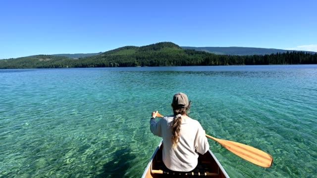 vídeos de stock e filmes b-roll de woman canoeing on a stunning mountain lake - destino de viagem