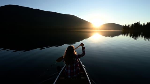 vídeos de stock e filmes b-roll de woman canoeing on a stunning mountain lake - caiaque barco a remos