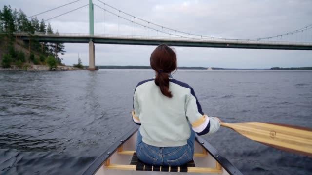 stockvideo's en b-roll-footage met het kanoën van de vrouw op meer in finland - recreatieboot